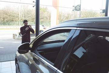 Salesman taking picture of car with mobile phone