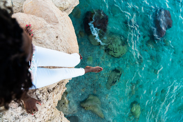 Woman sitting on cliff above water
