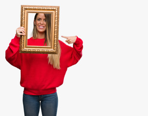 Beautiful young woman holding vintage frame very happy pointing with hand and finger