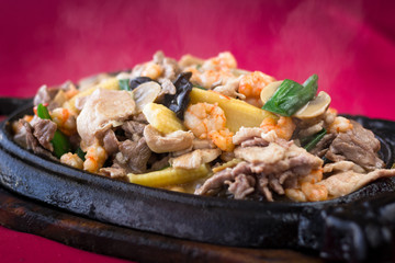 Close up on smokey meat sizzler with prawns, baby corn and mushrooms on iron black plate with wooden base on red tablecloth background. Traditional Chinese hot menu dish