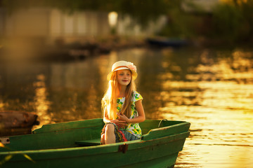 Cute little girl in a hat sitting in a boat on a lake at sunset