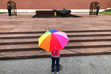 A girl stands in front of the Eternal Flame at the Kremlin in Moscow