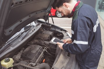 Male mechanic using digital tablet