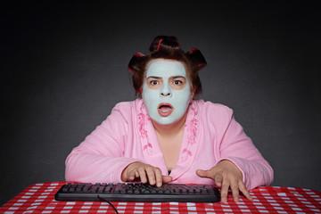 femme ronde et drôle avec bigoudis choquée par contenu ordinateur