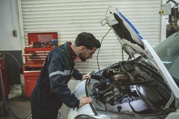 Side view of mechanic repairing car in garage