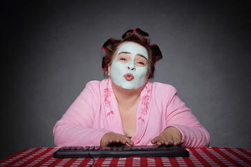 femme ronde et drôle avec bigoudis tapant sur un ordinateur et faisant un baiser