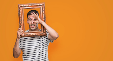 Handsome young man looking through vintage art frame with happy face smiling doing ok sign with hand on eye looking through fingers