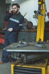 Mechanic talking on mobile phone