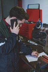 Mechanic writing on paper while talking on a mobile phone