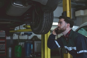 Male mechanic talking on mobile phone while examining car