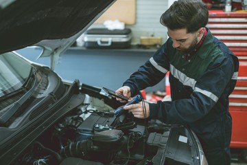 Mechanic taking picture of car engine with mobile phone