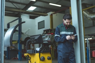 Mechanic using mobile phone in garage