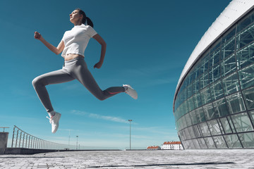 active young girl jumping outdoors, warming up and doing exercises