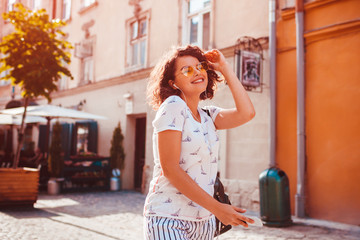 Beautiful young girl using smartphone and listening to the music walking on street. Woman dancing and singing