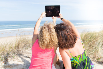 woman couple take selfie photo with a tablet on the beach