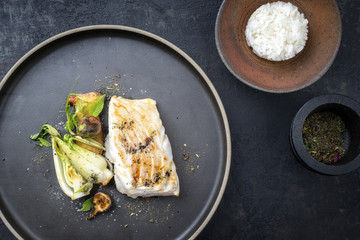 Modern Thai fried cod fish filet with bok choi and rice as top view on a plate