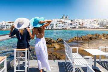 Zwei Freundinnen auf der Reise durch Griechenland genießen die Aussicht auf das Dorf von Naousa, Paros, Kykladen