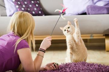 Junge Frau spielt mit Katze Fototapete