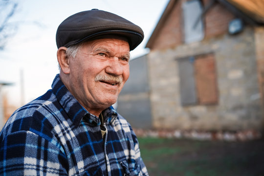 Happy smiling elder senior man portrait with a mustache in a cap on the background of a brick house in a Russian village