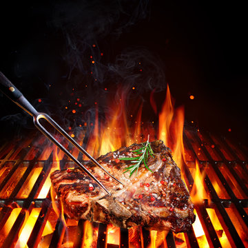 T-Bone Steak - Porterhouse  On Grill With Rosemary And Pink Pepper