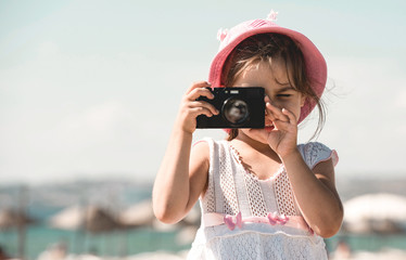 Happy Child Girl Tourist Taking Photos At Seaside In Summer