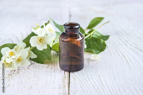 White flowers of jasmine syringa and dark glass vial with white flowers of jasmine syringa and dark glass vial with essential oil on white mightylinksfo