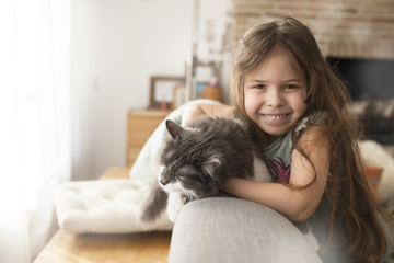little girl and cat at home on the couch. A happy child and a pet. Copy space.