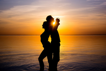 Young couple stand with their backs against each other in front of the sea at sunset