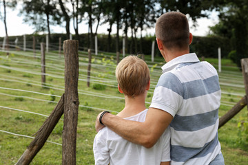 Father and son in vineyard. Two generations, family values. Summer holiday on farm, including kids in family business concept