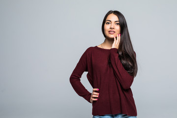Beautiful young businesswoman wearing glasses and thinking with hand on chin. Smiling pensive woman looking away isolated on grey background.