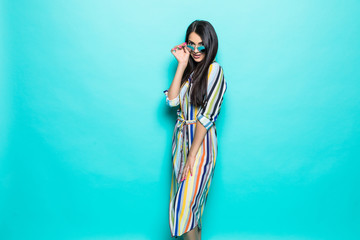 Fashion model in sunglasses , beautiful young woman isolated on blue background