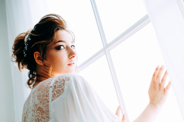 Tender elegant young bride with hairdo, hairpin and bridal makeup