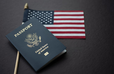 Flag of United States (American) next to Passport of USA on Black surface.