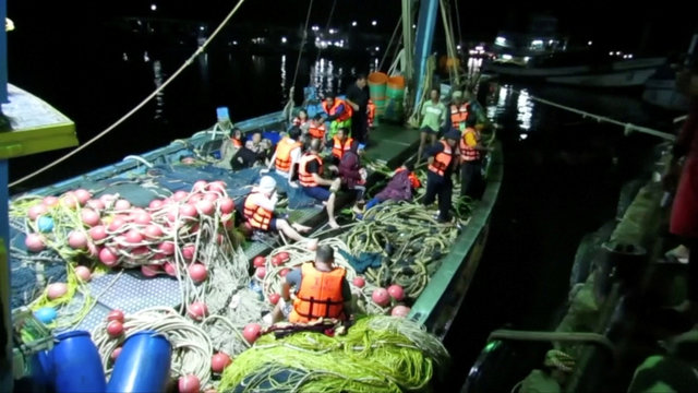 Rescued people in life jackets sit on a fishing boat after a boat they were travelling in capsized off the tourist island of Phuket