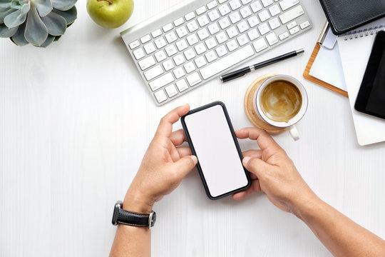 Man's hand holding white mobile phone  on desk in office