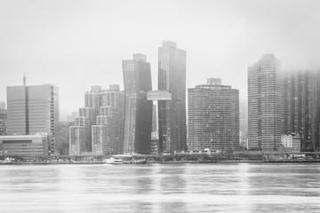 Foggy view of the Manhattan skyline from Gantry Plaza State Park, in Long Island City, Queens, New York City.