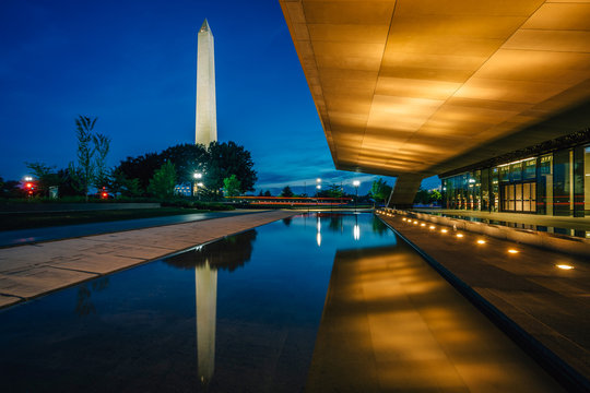 The Washington Monument and National Museum of African American History and Culture at night, in Washington, DC.