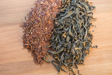 Rooibos and black tea leaves on wooden table, top view.