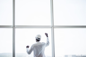 Young afro american man in protective hemlet standing in front of panoramic windows with reaised hands of victory and sucess