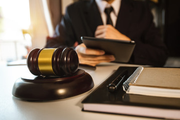 Justice and law concept.Male judge in a courtroom with the gavel,working with,digital tablet computer docking keyboard,eyeglasses,on black table
