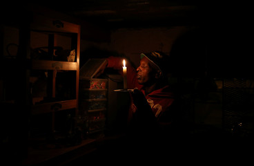 Siphiwe Ngubane uses a candle during a power outage, at his makeshift shop in Soweto