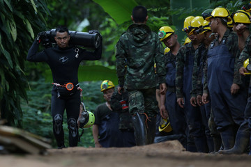 A diver carries an oxygen tank as he leaves the Tham Luang cave complex, where 12 boys and their soccer coach are trapped, in the northern province of Chiang Rai
