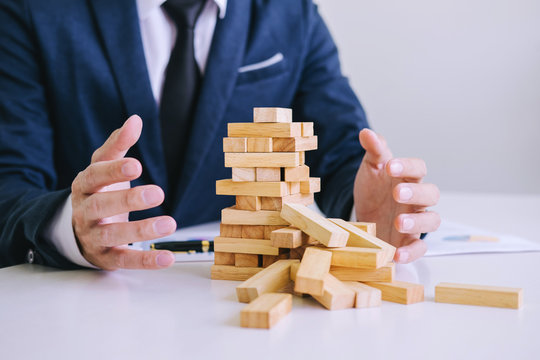 Alternative risk concept, plan and strategy in business protect with balance wooden stack with hand control risk shape