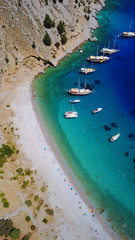 Aerial birds eye view photo taken by drone of famous tropical rocky beach of Agios Georgios with yachts docked, Symi island, Dodecanese, Greece