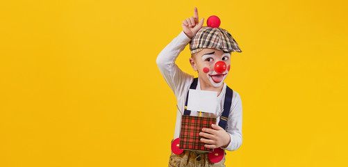 Funny kid boy clown fooling isolated yellow background,studio,blank,copy space for text,design,,advertising. Concept holiday,birthday,day laughter,jokes,1 april,party. Expression child face joy,smile.