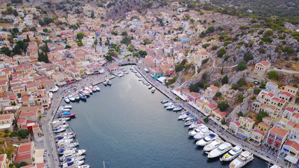 Aerial birds eye view photo taken by drone of Yalos, iconic port of Symi island at sunset with beautiful clouds, Dodecanese, Greece