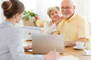 Smiling elderly man and woman purchasing a trip at the travel agency