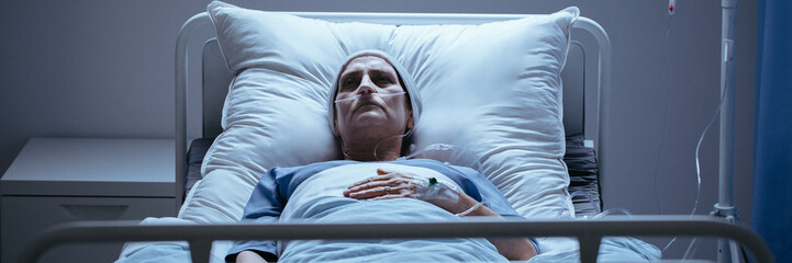 Cover photo of a lonely, sick woman lying on a hospital bed with a breathing tube and head scarf