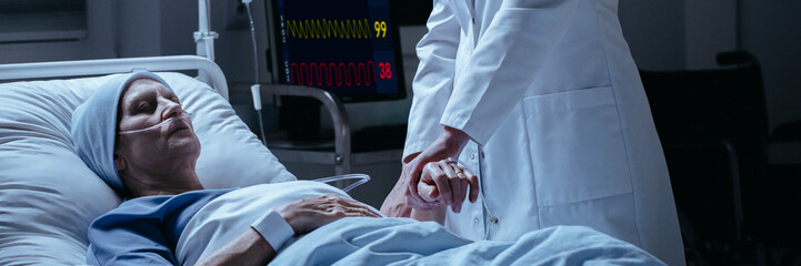 Close-up of a doctor checking pulse of his dying of cancer patient in the hospital