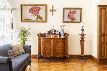 Posters of roses above wooden cabinet in elegant living room interior with blue sofa. Real photo